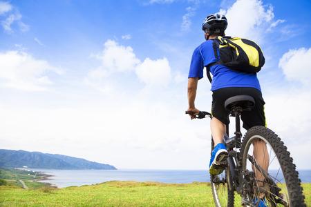 マウンテン バイクに座っていると海を探している若い男 写真素材