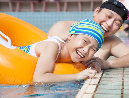 swim: niña feliz aprendiendo a nadar en la piscina con el padre