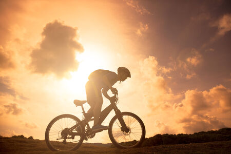 The silhouette of mountain bicycle rider on the hill photo