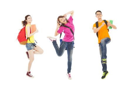 adolescente: estudiantes felices escuchando música y saltando con los libros Foto de archivo