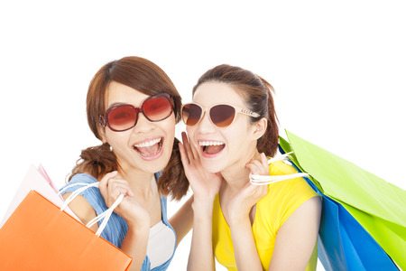 smiling young sisters holding shopping bags photo