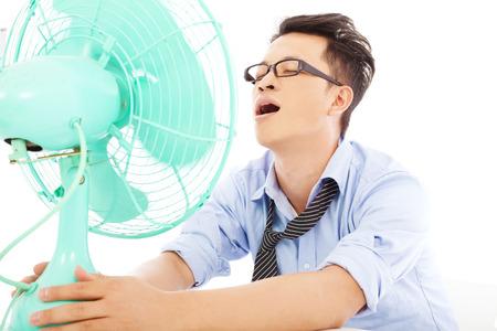 ビジネスの男性ファンとホット夏の暑さに苦しんでいます。