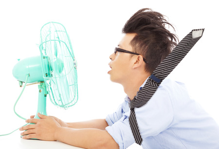 Summer heat, business man use fans to cool down photo