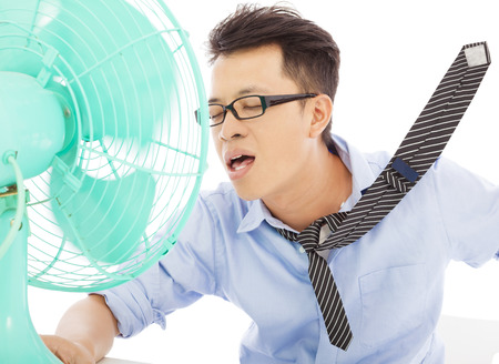 Young man cooling face under wind of fan Stok Fotoğraf
