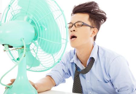 若いビジネスマンを冷却するファンを使用します。