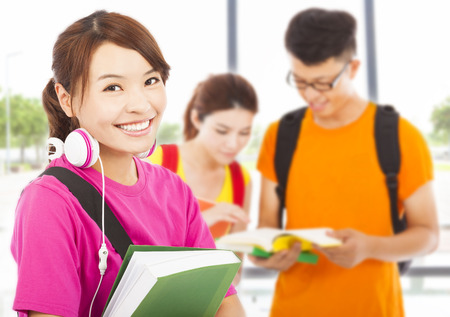 student: young student holding books and earphone with classmates