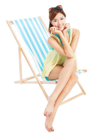 young woman smiling and sitting on a beach chair photo