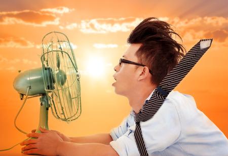 熱の波が来ている、電動ファンを持ってビジネス男