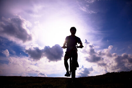 mountain bicycle rider on the hill with sunrise background photo