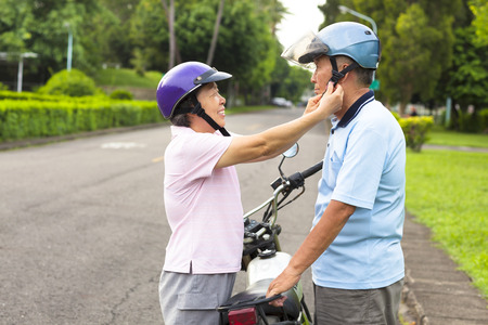 happy grandmother help grandfather to wear a helmet Stock Photo - 29618805