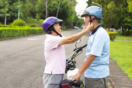 happy grandmother help grandfather to wear a helmet