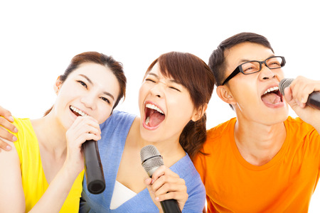 happy asian young group having fun singing with karaoke photo
