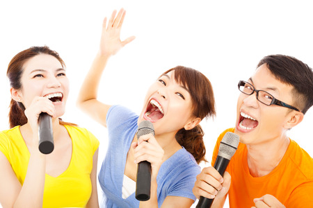 singing: happy asian young group having fun singing with microphone