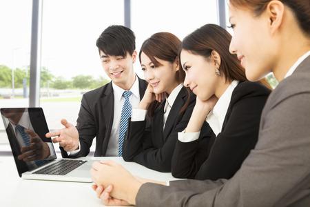 비즈니스 사람이 동료에게 보고서를 제시하는 노트북을 사용