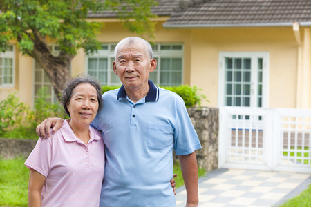 happy asian senior couple standing in front of a house