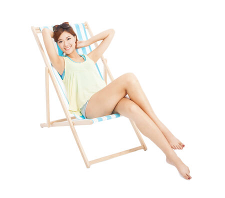 beauty sunshine girl smiling and lying on a beach chair photo