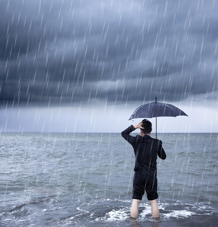 downpour: upset business man holding a umbrella with cloudburst background