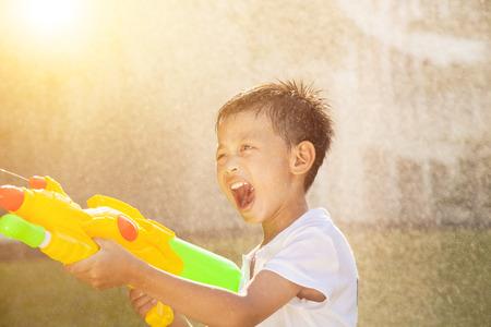 reir: feliz niño gritando y jugando pistolas de agua en el parque Foto de archivo