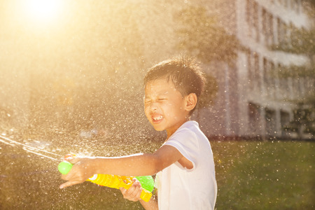 children playing outside: Cheerful little boy playing water guns in the park