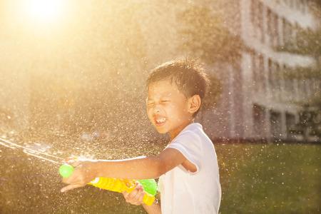 jugando: Ni�o peque�o alegre que juega pistolas de agua en el parque Foto de archivo