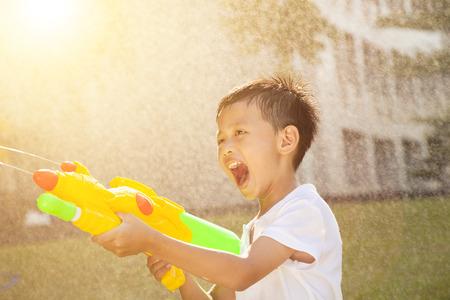 어린 소년은 소리와 공원에서 물 총을 재생 스톡 콘텐츠