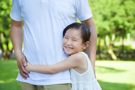 smiling little girl hug father waist in the park photo