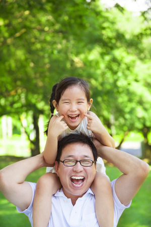 asian trees: little girl sitting father shoulder and make a funny facial expression Stock Photo