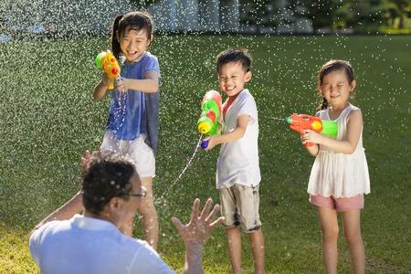 kleine jongens met behulp van waterkanonnen om hun vader te spuiten Stockfoto