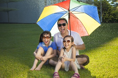 Father and two daughters sitting on a meadow with colorful umbrella photo