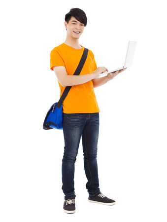 laptop stand: happy young student standing and using laptop Stock Photo