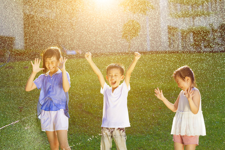 Happy kids has fun playing in water fountains photo
