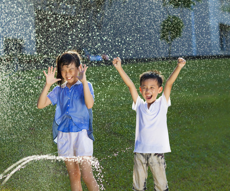 kids playing water: excited kids has fun playing in water fountain Stock Photo