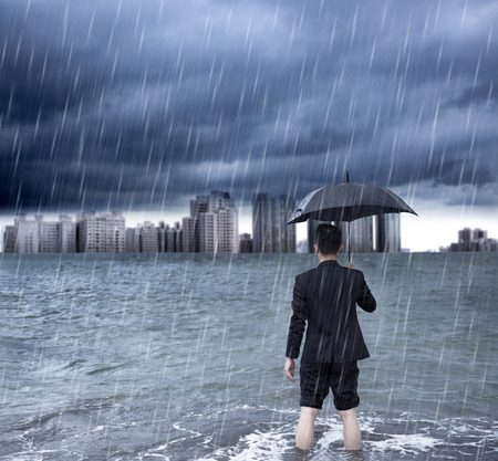 scourge: business man holding an umbrella and standing  with cloudburst background