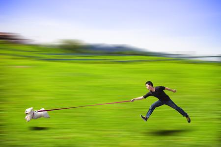 perro desobediente corriendo rápido y arrastrando a un hombre por la correa