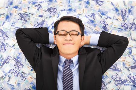 Business Mann genießt und auf den Stapel von Geld liegen