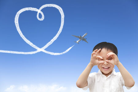 happy boy watching airplane flying and drawing a heart of cloud photo
