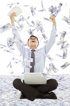 financial freedom: business man winning a lottery with money rain background