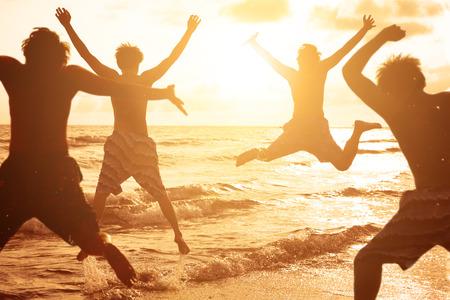 grupo de jóvenes que saltan en la playa con el atardecer de fondo