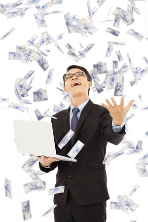 happy business man holding a laptopa and  catching money Stock Photo - 30203152