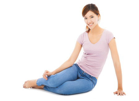happy and beautiful young student sitting on the floor photo