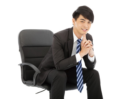 Young businessman thinking and sitting in a chair photo