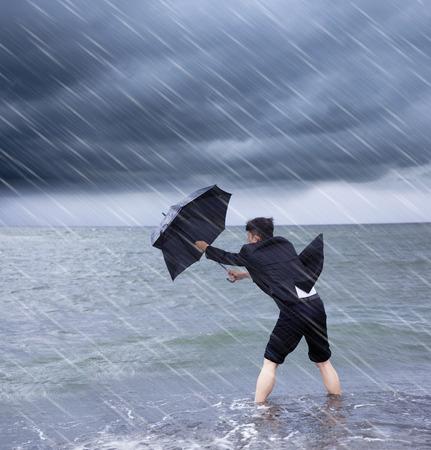 business man met een paraplu naar regenbui weerstaan