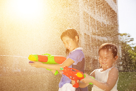 ni�as jugando: Muchachas alegres que juegan pistolas de agua en el parque Foto de archivo