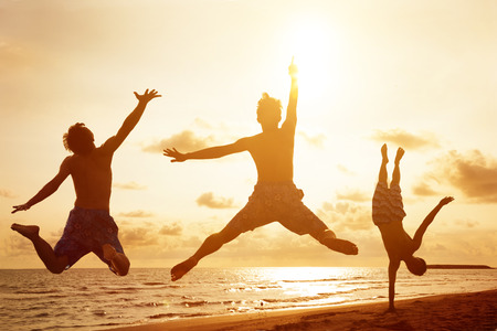 morning sky: giovani che saltano sulla spiaggia con sfondo tramonto Archivio Fotografico