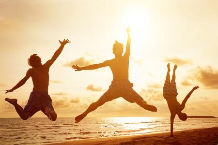 människor: ungdomar hoppar på stranden med solnedgången bakgrund Stockfoto