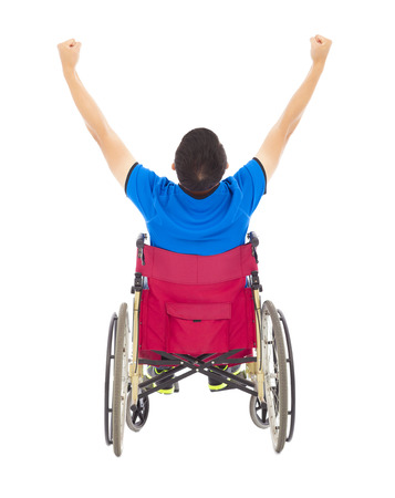handicapped man sitting on a wheelchair and raise arms