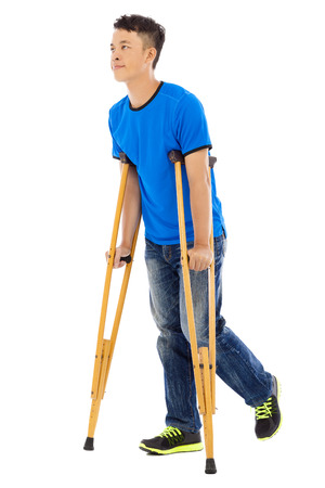 orthopaedic: Young asian man on crutches. white background