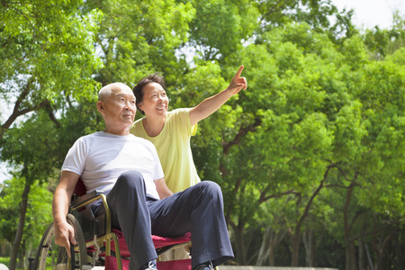Asian senior man sitting on a wheelchair with his wife photo