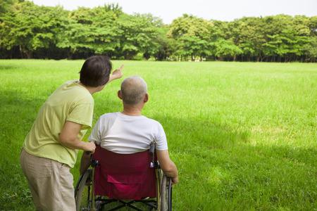 senior man zittend op een rolstoel met zijn vrouw