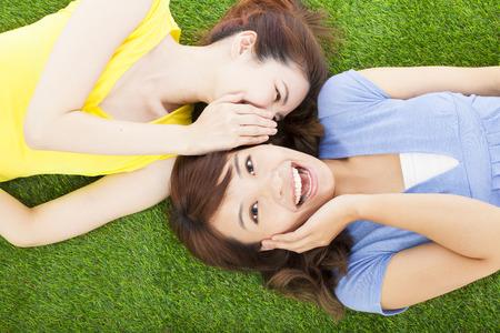 amigas conversando: dos hermanas que susurran chisme en la hierba